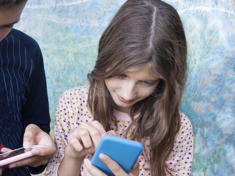 Дети занятые с мобильными телефонами стоковая фотография