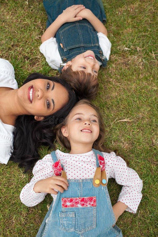 дети засевают счастливо ее лежа мать травой стоковое фото