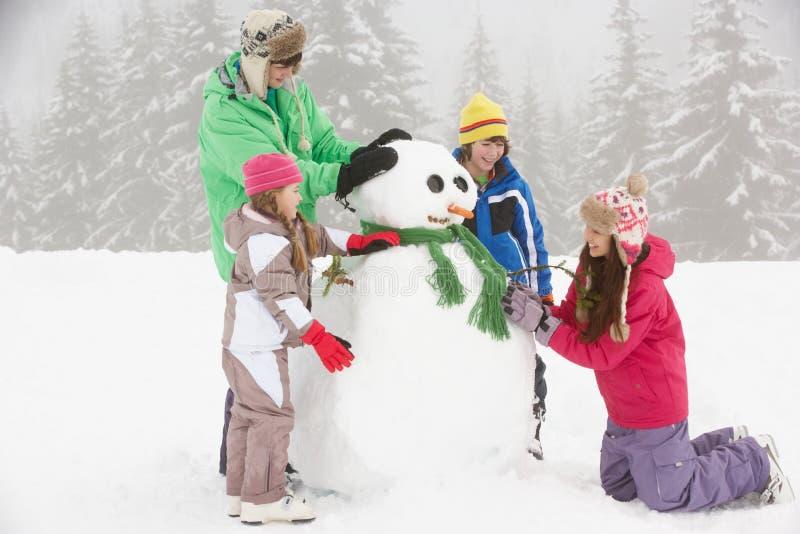 дети здания собирают снеговик лыжи праздника стоковое изображение