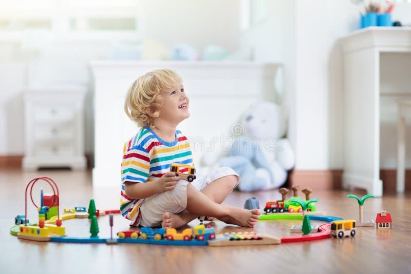 Дети играют деревянную железную дорогу Ребенок с поездом игрушки стоковая фотография