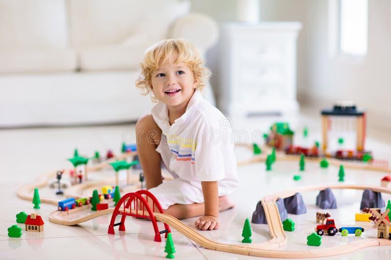 Дети играют деревянную железную дорогу Ребенок с поездом игрушки стоковое фото rf