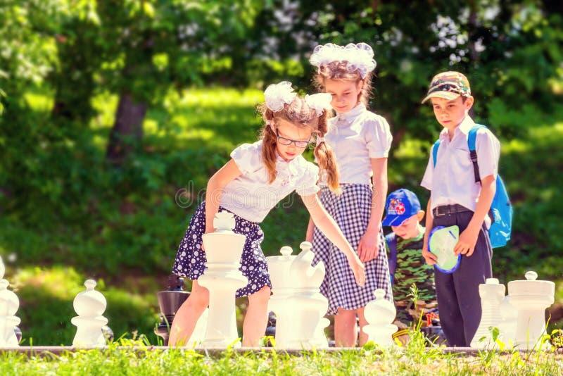 Дети играют на открытом воздухе шахматы в парке на день лета солнечный стоковые фото