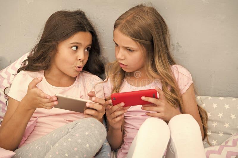 Дети играют применение игры смартфона мобильное Концепция применения смартфона Girlish партия пижамы отдыха Девушки стоковые изображения rf