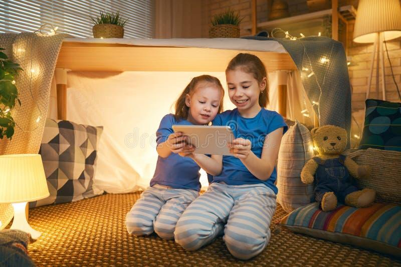 Дети играют с планшетом в шатре стоковое фото rf