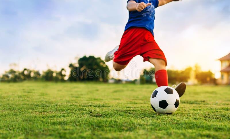 Дети играют футбол футбола для тренировки под солнечным светом Стиль изображения силуэта и фильма стоковые фото
