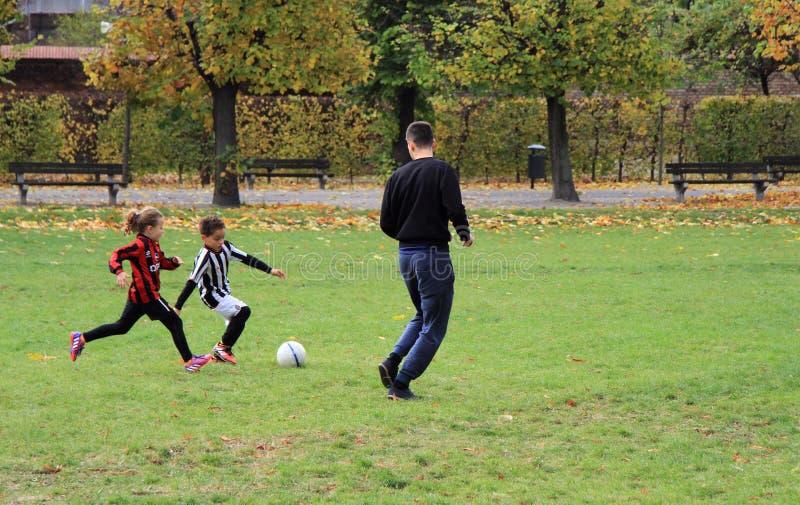 Дети играют футбол в парке города стоковые фотографии rf