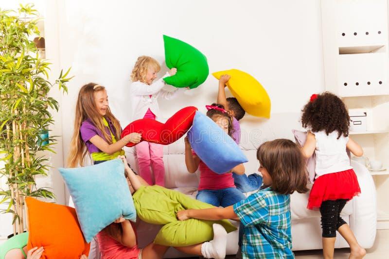 Дети играя бой подушками стоковые фотографии rf