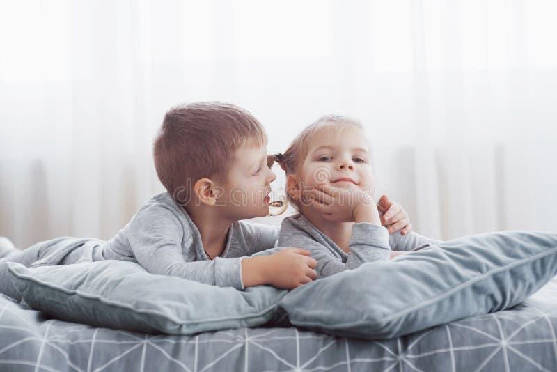 Дети играя в кровати родителей Дети просыпают вверх в солнечной белой спальне Игра мальчика и девушки в соответствуя пижамах slee стоковые изображения rf