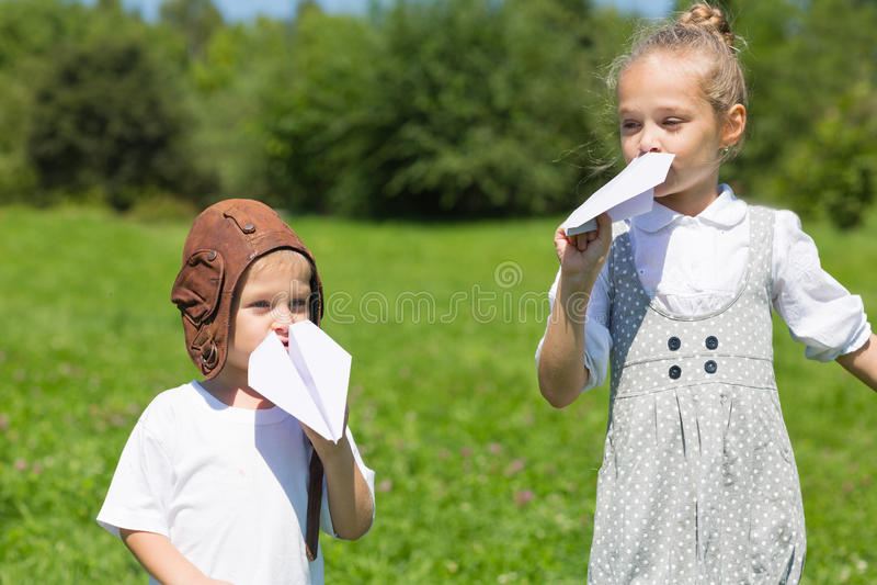 Дети играя в плоскости бумаги outdoors стоковое фото rf