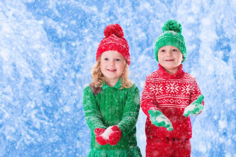 Дети играя в снежном лесе зимы стоковые изображения