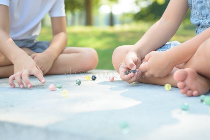 Дети играя игру мраморов снаружи стоковое изображение