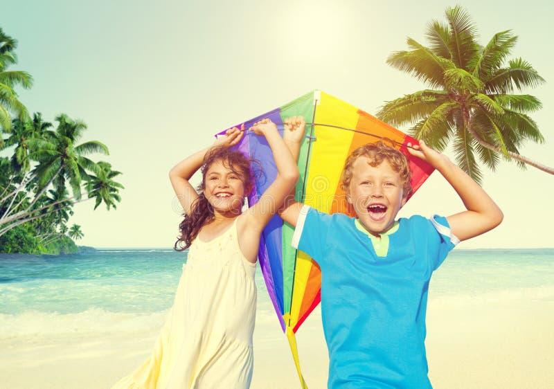 Дети играя концепцию лета пляжа счастья змея жизнерадостную стоковые изображения