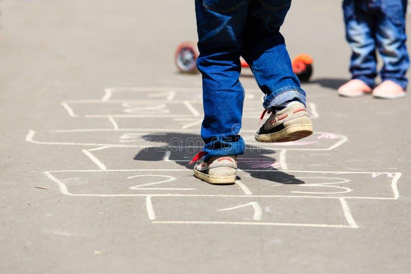 Дети играя классики на спортивной площадке outdoors стоковые фото