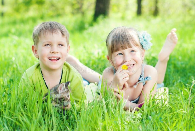 Дети играя на зеленой траве в парке стоковые фотографии rf