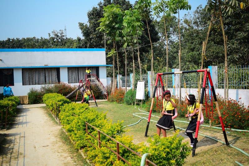 Дети играя на школьной форме земли школы нося стоковое изображение rf