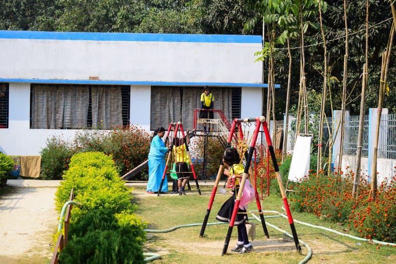 Дети играя на школьной форме земли школы нося стоковая фотография rf