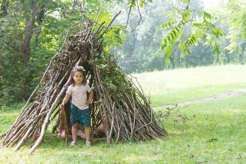 Дети играя рядом с деревянной ручкой расквартировывают выглядеть как индийская хата, стоковые изображения