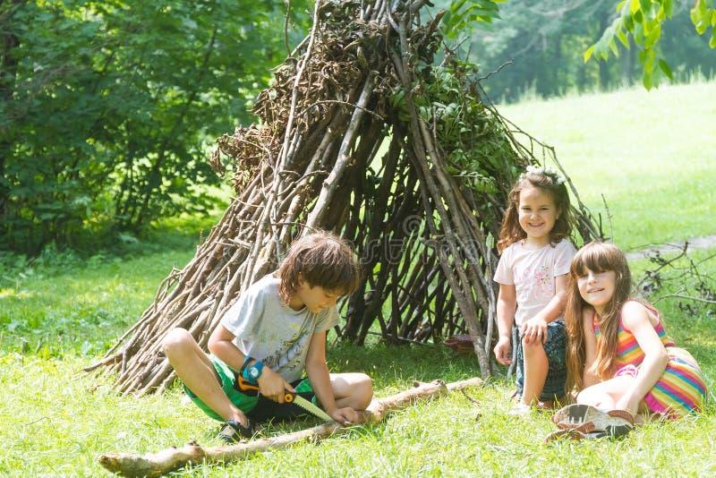 Дети играя рядом с деревянной ручкой расквартировывают выглядеть как индийская хата, стоковая фотография rf