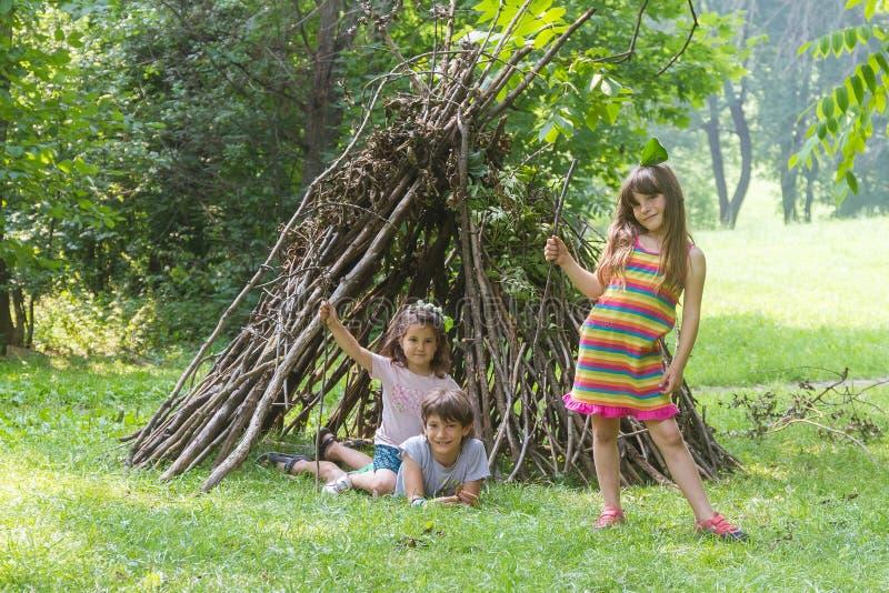Дети играя рядом с деревянным домом ручки стоковая фотография rf
