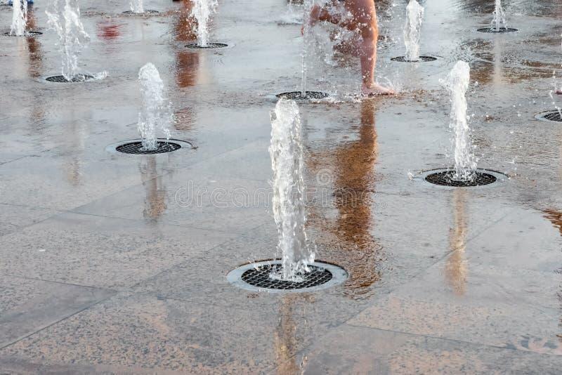 Дети играя с водой в фонтане парка Счастливые дети имеют потеху играя в фонтанах горячее лето стоковая фотография