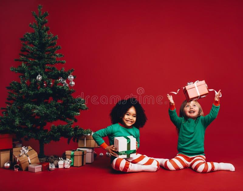 Дети играя с подарочными коробками рождества стоковые изображения rf