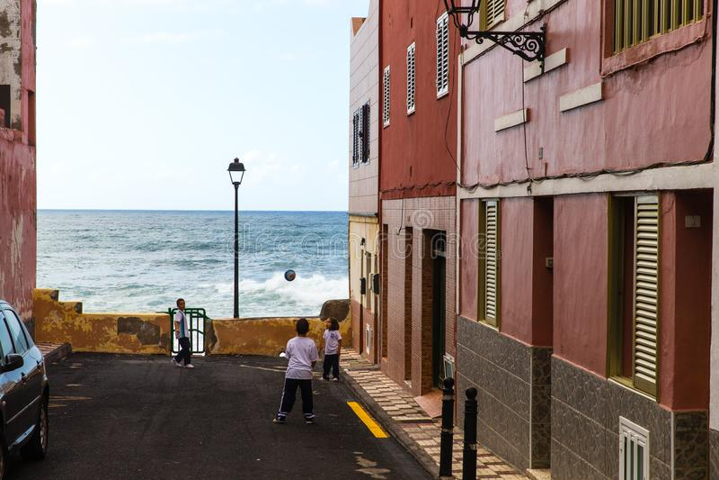 Дети играя футбол около моря в Puerto de Ла cruz в Тенерифе, Испании стоковые фото