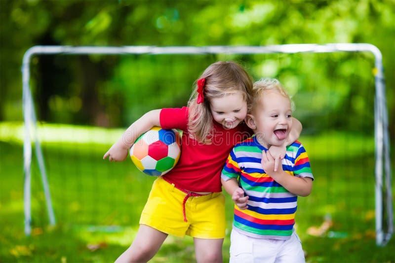 Дети играя футбол в парке стоковое изображение