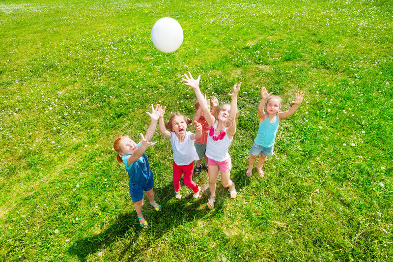 Дети играя шарик на луге стоковое фото