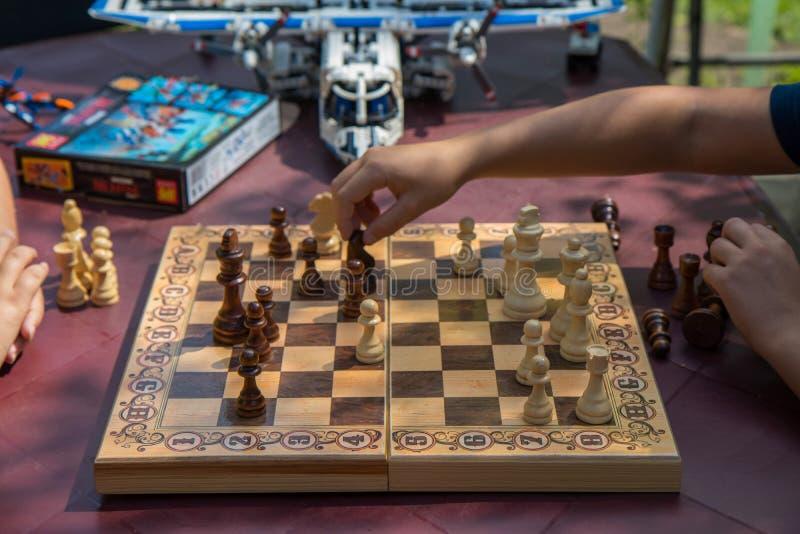 Дети играя шахмат в саде с запачканными игрушками на предпосылке стоковое изображение