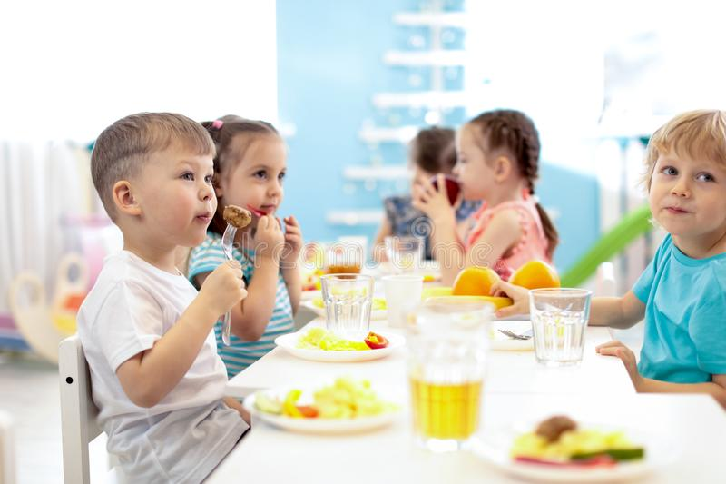 Дети имеют обед в центре daycare Дети есть здоровую еду в детском саде стоковая фотография