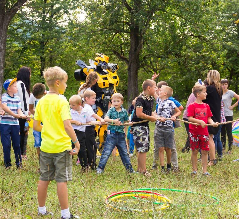Дети имеют потеху и игру с аниматором в шмеле трансформатора костюма стоковые фото