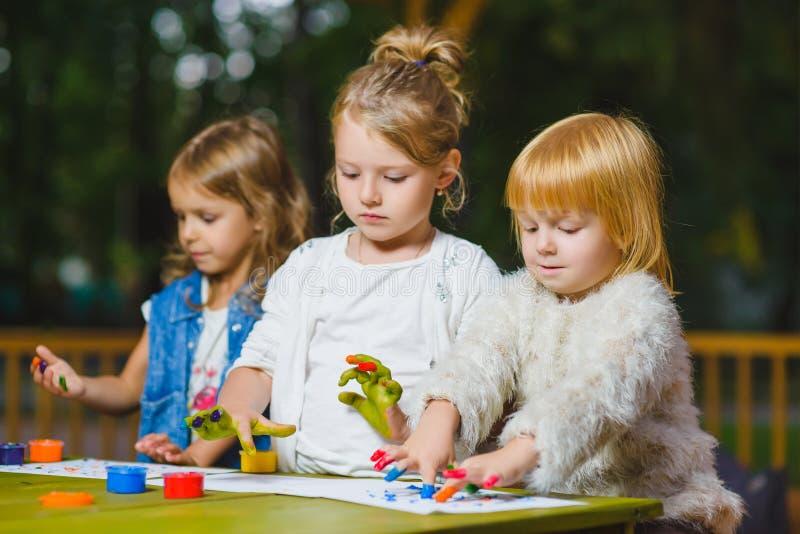 Дети имея картину потехи с краской пальца стоковая фотография