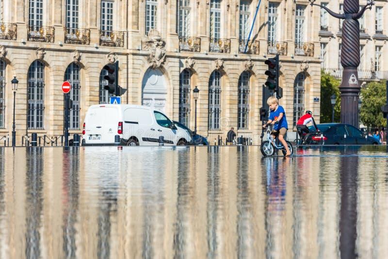 Дети имея потеху в фонтане зеркала в Бордо стоковое изображение rf