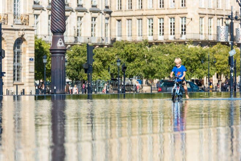 Дети имея потеху в фонтане зеркала в Бордо стоковая фотография