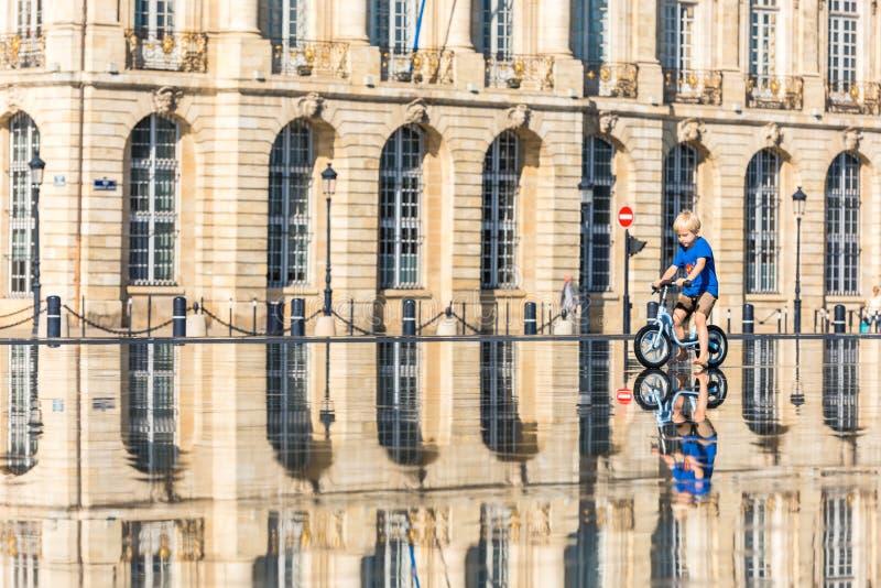 Дети имея потеху в фонтане зеркала в Бордо стоковые изображения rf