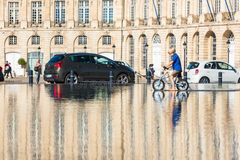 Дети имея потеху в фонтане зеркала в Бордо стоковое фото rf