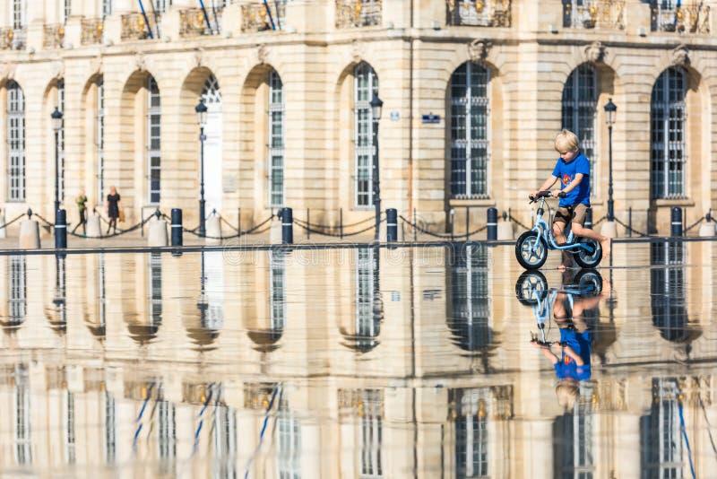 Дети имея потеху в фонтане зеркала в Бордо стоковые фото