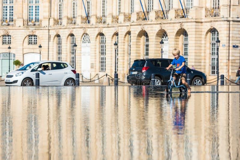 Дети имея потеху в фонтане зеркала в Бордо стоковые изображения
