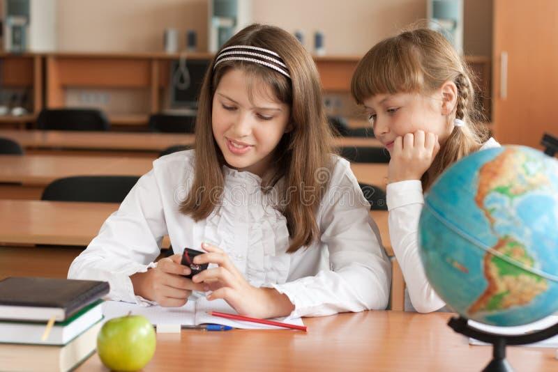 дети интересуют смотреть мобильный телефон стоковые фотографии rf