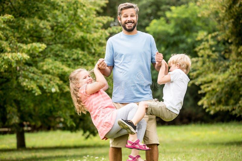 Дети и игра отца как семья стоковая фотография rf