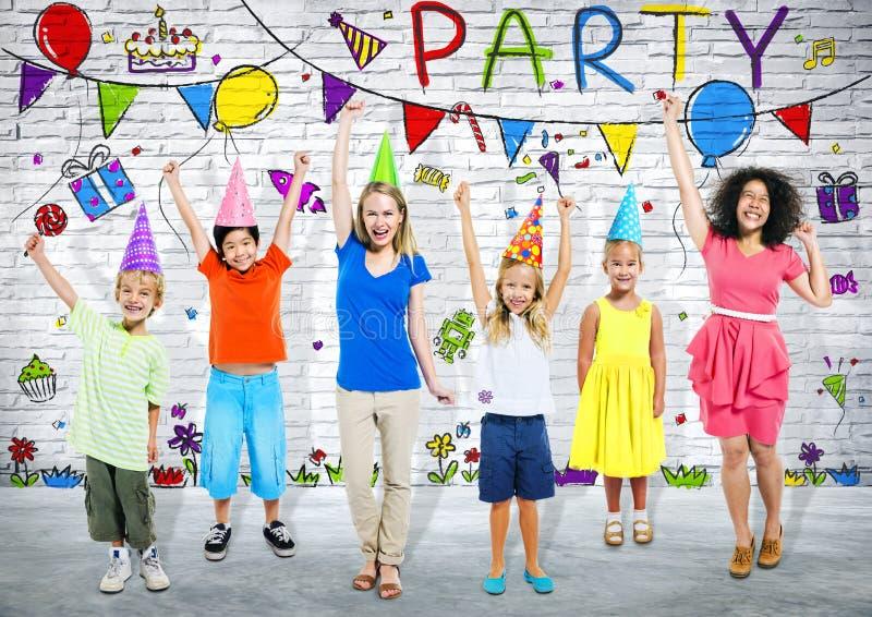 Дети и молодой взрослый в вечеринке по случаю дня рождения стоковые изображения