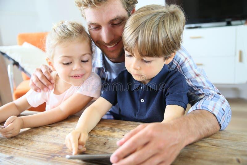 Дети и отец играя с smartphone стоковые изображения rf