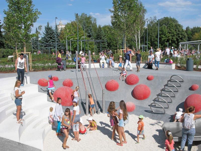 Дети и родители на спортивной площадке, активные остатки в парке стоковое фото