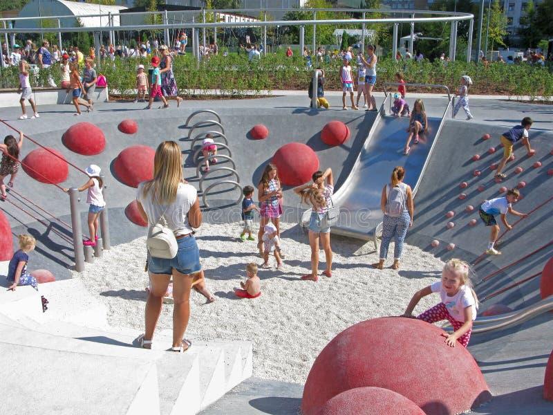 Дети и родители на спортивной площадке, активные остатки в парке стоковые фотографии rf