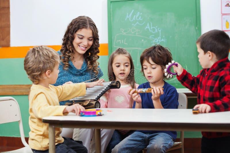 Дети и учитель играя с мюзикл стоковые изображения rf