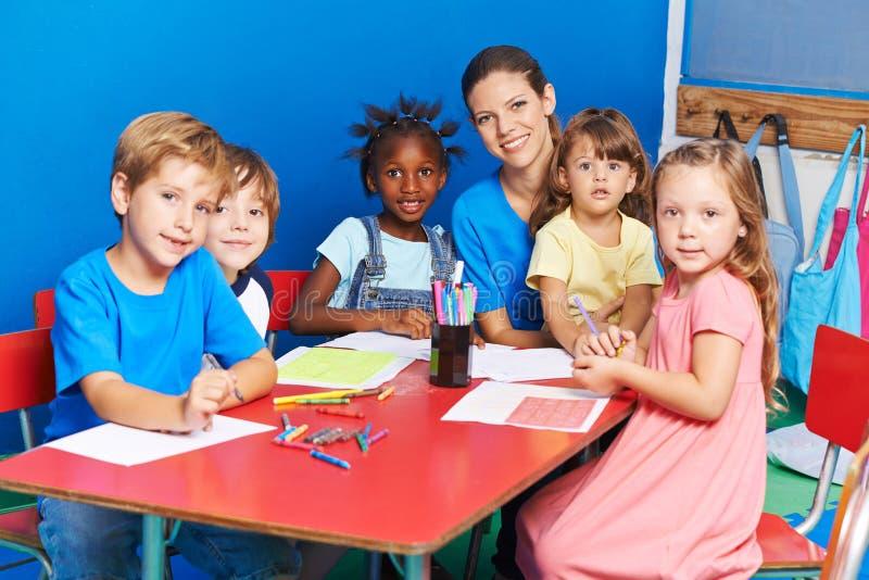 Дети крася в детском саде стоковое изображение