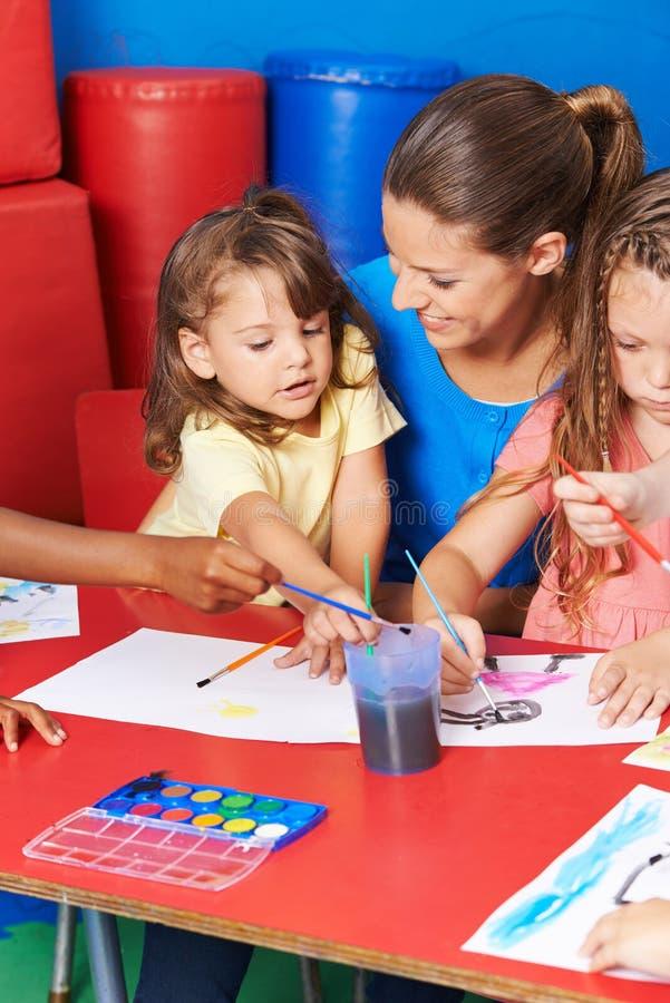 Дети крася изображения в уходе за детями стоковое изображение