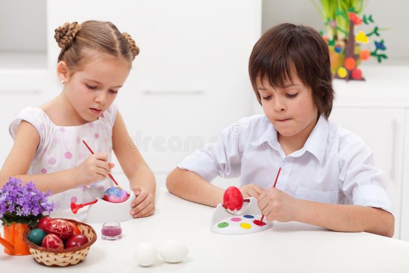 Дети крася пасхальные яйца стоковая фотография rf