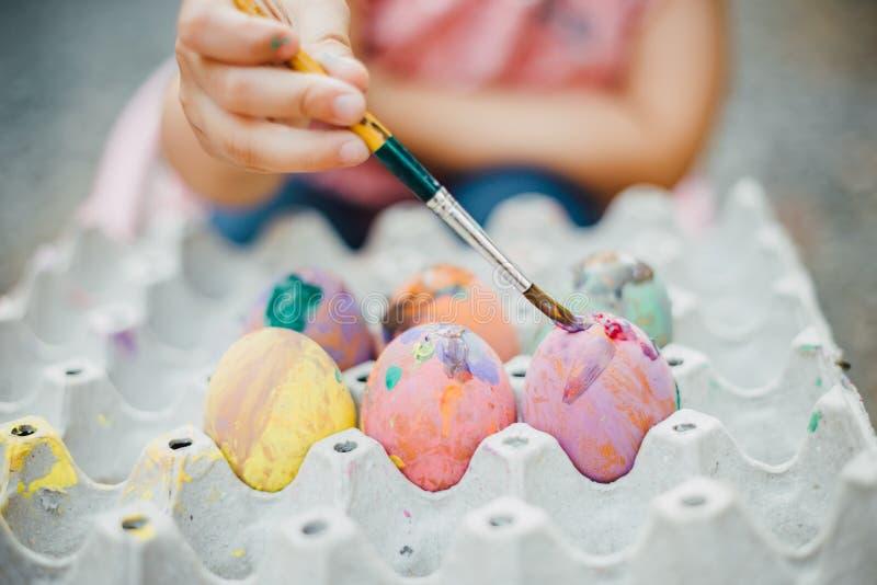 Дети крася яйцо на день пасхи стоковое фото