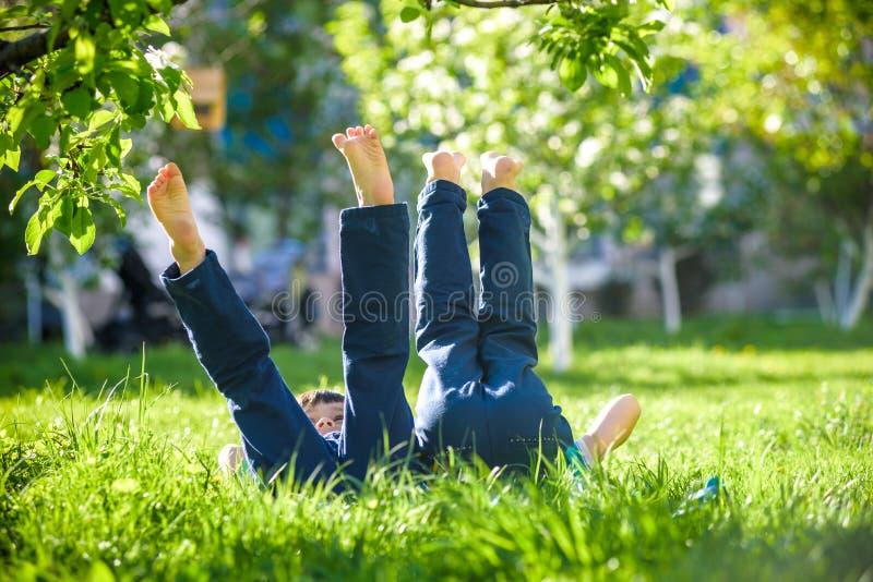Дети лежа на зеленой траве в парке на летний день с их ногами поднялись до неба стоковые фото